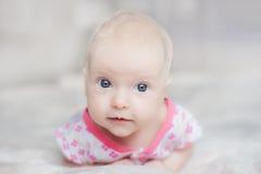 在白色床上的逗人喜爱的婴孩 免版税图库摄影