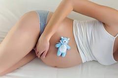 在白色床上的年轻人怀孕的女孩 免版税库存图片