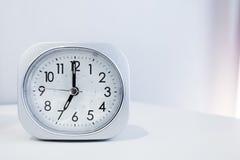 在白色床立场的白方块时钟有白色墙纸背景,在最小的样式装饰的早晨时间 免版税库存照片