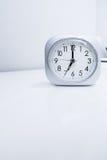 在白色床立场的白方块时钟有白色墙纸背景,在最小的样式装饰的早晨时间 图库摄影