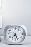 在白色床立场的白方块时钟有白色墙纸背景,在最小的样式装饰的早晨时间 库存照片
