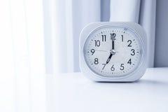 在白色床立场的白方块时钟有白色帷幕背景,在最小的样式装饰的早晨时间 免版税库存图片