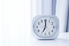 在白色床立场的白方块时钟有白色帷幕背景,在最小的样式装饰的早晨时间 库存照片