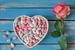 在白色心形的碗和白玫瑰的五颜六色的糖果在w 免版税图库摄影