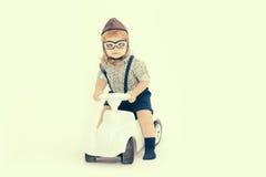 在白色或飞行员隔绝的小男孩司机 免版税库存图片