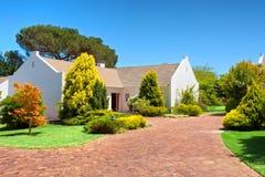 在白色房子前面的红砖正方形 免版税库存图片