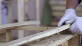 在白色手套的大师与木家具一起使用 老钉子特写镜头  大师驾驶钉子入委员会,然后 影视素材