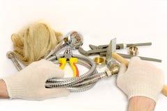 在白色手套,修理供水的工具的人的手s 免版税库存图片