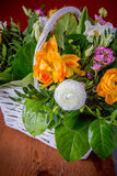 在白色手工制造篮子的美丽的花 库存图片