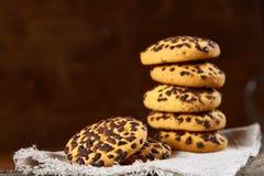 在白色手织的餐巾的被堆积的巧克力曲奇饼在乡村模式,选择聚焦 图库摄影