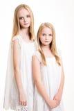 在白色打扮的两个美丽的白肤金发的十几岁的女孩 免版税库存照片
