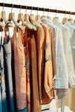 在白色挂衣架的淡色编织光夏天礼服 库存照片