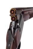 在白色有两个蓝色弹药筒后方特写镜头视图隔绝的被打开的双桶的狩猎枪 库存照片