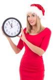 在白色有时钟摆在的隔绝的圣诞老人帽子的少妇 免版税库存图片