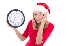 在白色有时钟摆在的隔绝的圣诞老人帽子的惊奇的妇女 免版税库存图片