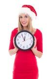 在白色有时钟摆在的隔绝的圣诞老人帽子的愉快的妇女 免版税库存图片