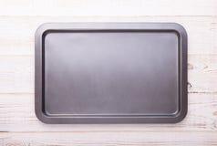 在白色木书桌上的空的烘烤盘子 免版税库存照片