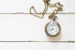 在白色木地板上的美丽的古铜色手表项链 库存照片