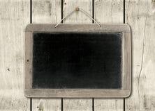 在白色木墙壁背景的黑板 图库摄影