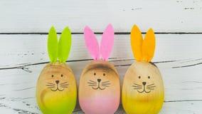 在白色木头的三个兔宝宝 图库摄影