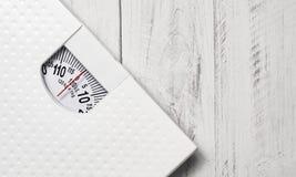 在白色木头的重量标度 免版税库存图片