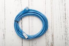 在白色木头的顶视图蓝色usb缆绳 库存图片
