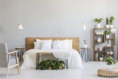 在白色木床附近的被仿造的扶手椅子在与蒲团和植物的灰色卧室内部 实际照片 免版税库存图片