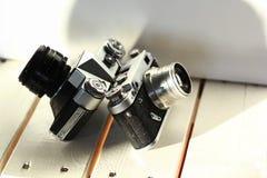 在白色木板条,被日光照射了内部的两台黑老学校葡萄酒照片照相机 库存照片