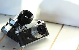 在白色木板条,被日光照射了内部的两台黑老学校葡萄酒照片照相机 图库摄影