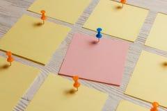 在白色木板的固定式,空白的色的贴纸Pined 定期管理,计划 库存照片