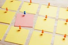 在白色木板的固定式,空白的色的贴纸Pined 定期管理,计划 免版税库存图片