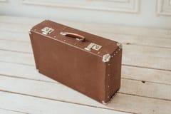 在白色木板走道地板上的老棕色手提箱 免版税库存图片