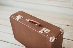 在白色木板走道地板上的老棕色手提箱 库存照片