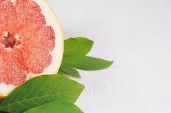 在白色木板,宏指令,拷贝空间的五颜六色的水多的切片葡萄柚和绿色叶子 免版税库存照片