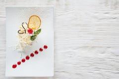 在白色木桌上的乳脂状的橙色点心 免版税图库摄影