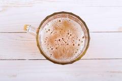 在白色木桌上的储藏啤酒杯子 库存图片