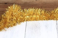 在白色木桌上的圣诞节金黄链子有棕色背景 库存照片