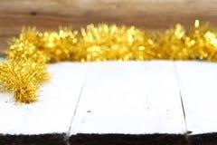 在白色木桌上的圣诞节金黄链子有棕色背景 免版税库存图片