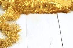 在白色木桌上的圣诞节金黄链子 免版税库存照片