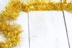在白色木桌上的圣诞节金黄链子 免版税图库摄影