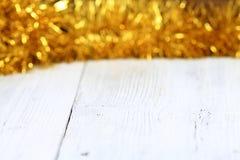 在白色木桌上的圣诞节金黄链子 免版税库存图片