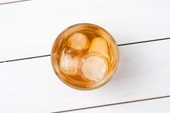 在白色木桌上的威士忌酒玻璃 库存图片