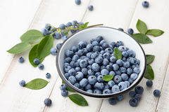 在白色木桌上的新鲜的蓝莓碗 库存照片