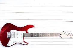 在白色木桌上的红色电吉他 库存图片
