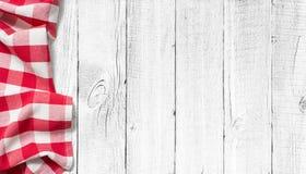 在白色木桌上的红色野餐桌布 免版税图库摄影