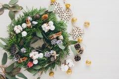 在白色木桌上的自创圣诞节花圈 免版税库存图片