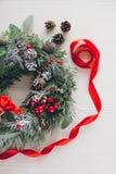 在白色木桌上的自创圣诞节花圈 免版税库存照片