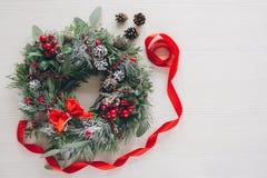 在白色木桌上的自创圣诞节花圈 库存图片