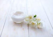 在白色木桌上的花秀丽奶油围拢的罐 免版税库存照片
