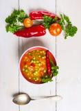 在白色木桌上的蔬菜通心粉汤汤与菜和匙子 库存图片